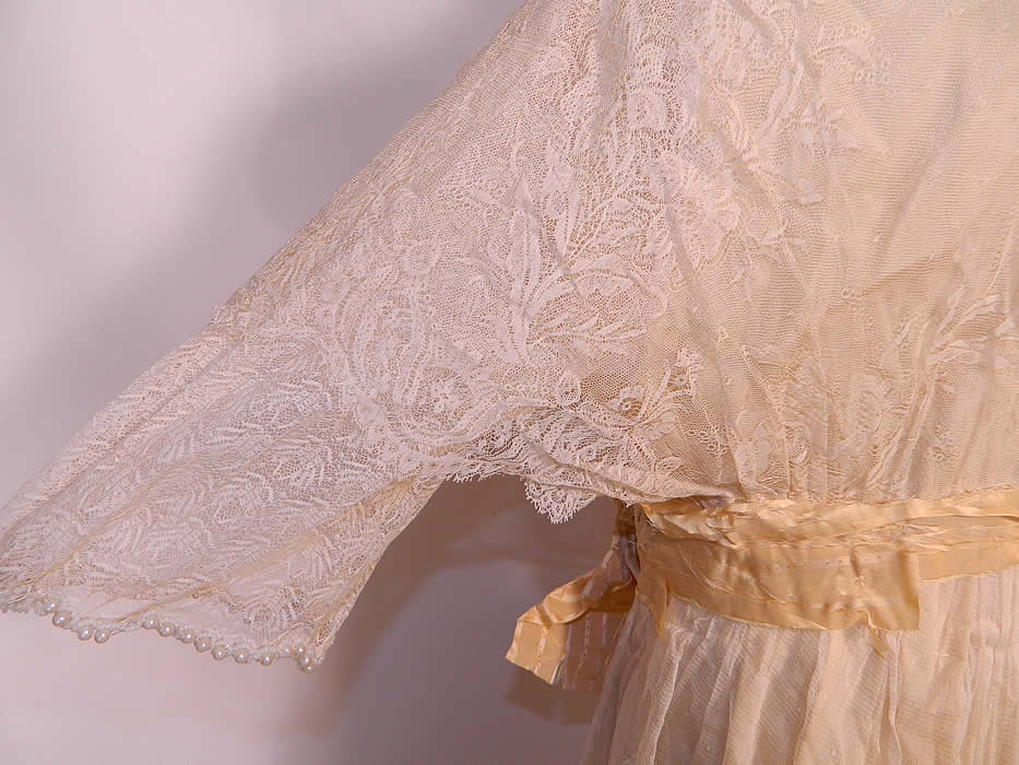 Edwardian Titanic Cream Silk Lace Pearl Beaded Wedding Gown Dress. This beautiful bridal wedding gown dress has a layered, tiered style, with sheer lace insert necklines, 3/4 length sleeves, an attached ribbon belted sash, long floor length wrap style skirt with side drape and snap closures.