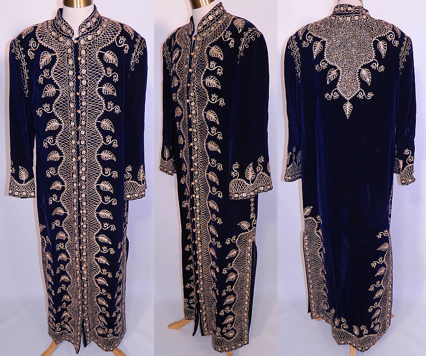 Vintage Adonis Lebanon Blue Velvet Gold Embroidered Boho Kaftan Robe Coat. It is made of a dark blue velvet fabric, with gold metallic braiding soutache embroidery work done in a decorative ethnic scrolling, spiral, vine leaf pattern design. This exquisite ethnic hippie chic, bohemian, loose fitting kaftan style robe coat is a long floor length, with long full sleeves, shoulder padding, side slits skirted bottom, fully lined and gold metallic knotted buttons with loop closures all the way down the front