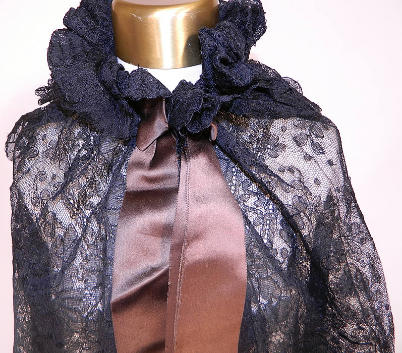 Victorian Antique Black Chantilly Lace Layered Shawl Cloak Cape. This lovely lace cloak cape was created from a shawl, with a layered tiered back, gathered ruffle neck collar with hook closure, brown silk satin ribbon bow trim and is sheer, unlined. The cape measures 32 inches long in the front, 22 inches long in the back, with a 50 inch bust, 18 inch neck and 110 inch bottom circumference.