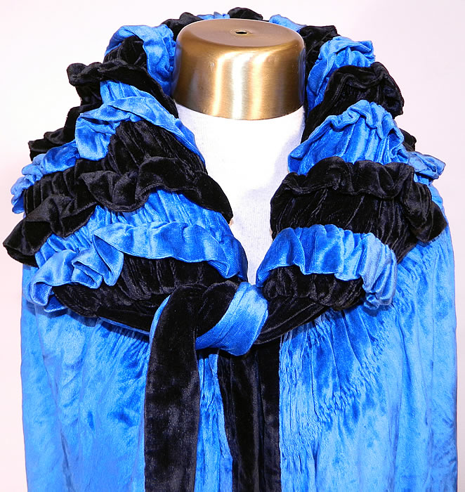 Vintage Gatsby Blue & Black Velvet Reversible Fringe Cocoon Opera Cloak Cape. This gorgeous long opera cloak cape is loose fitting with a cocoon wrap style, matching velvet fabric neck tie closure and large shawl style collar. The cape measures 40 inches long, with 20 inch long fringe and is 70 inches in circumference. It is in excellent condition. This is truly a wonderful piece of wearable art!