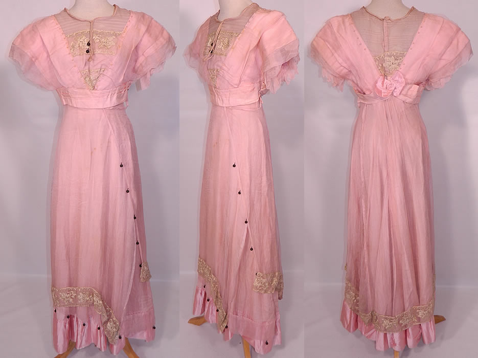 Edwardian Titanic Pink Silk Pearl Beaded Lace  Evening Gown Dress. This Edwardian Titanic era pink silk pearl beaded lace evening gown dress dates from 1912. It is made of a pastel pink silk fabric, with a sheer pink silk chiffon overlay, cream color embroidered net lace, pink pearl, black silk ball trim accents.