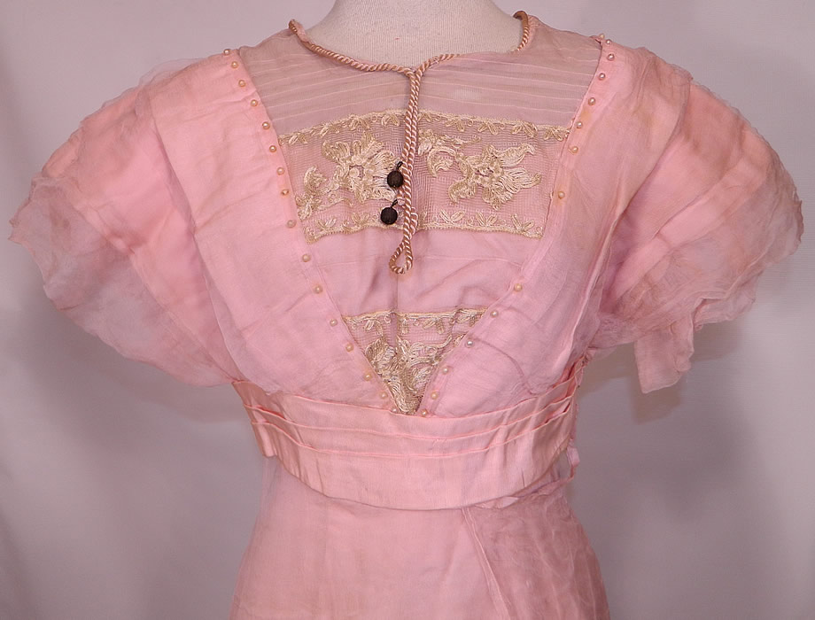 Edwardian Titanic Pink Silk Pearl Beaded Lace  Evening Gown Dress. This pretty pink evening ball gown dress has a long floor length layered asymmetrical skirt, a pleated layered trim top, short sleeves, pink back bow trim belted sash waist, hook closures on the back and is fully lined.