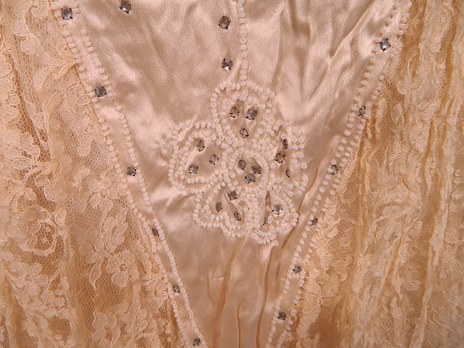 Vintage Robe de Style Cream Silk Rhinestone Beaded Lace Pannier Hoop Wedding Dress. It has a drop waist style which comes to a point, short cap sleeves, a pannier hoop sewn inside along the sides creating a low and wide flared hips style and layered lace ruffle skirt.