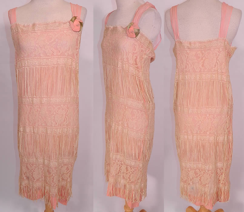 Vintage Cream Fringe Filet Lace Pink Silk Rosette Chemise Slip Flapper Dress. This exquisite vintage cream fringe filet lace pink silk rosette chemise slip flapper dress dates from the 1920s. It is made of a pale pink silk chiffon slip lining underneath, with an off white cream color sheer fine unique fringed filet lace floral pattern fabric overlay.