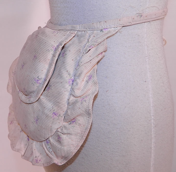 Victorian White Cotton Pique Purple Violet Polka Print Crinolette Bustle Pad Support. This pretty pad is created in a puffed pillow crescent shape, with a layered double pad design and ruffle trim edging. There is a cotton cloth strap tie belt around the waist.
