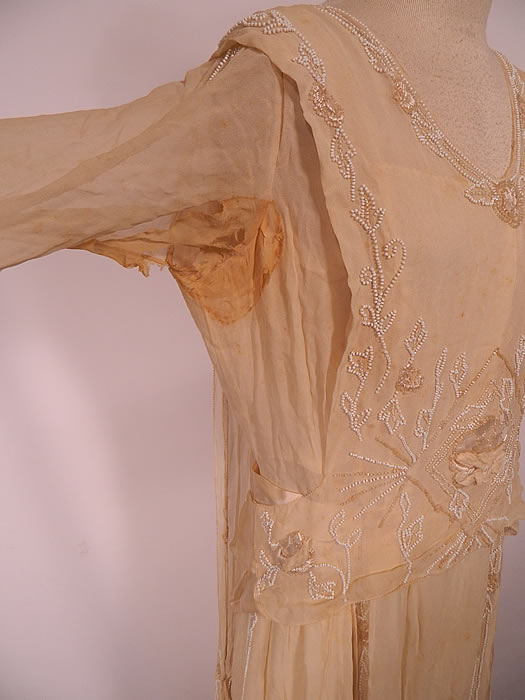 Edwardian Cream Silk White Beaded Rosette Belted Wedding Gown Dress. It is in as-is fair condition, has not been cleaned, with several small faint age spots yellowing stains in areas and frayed stained underarms (see close-up).