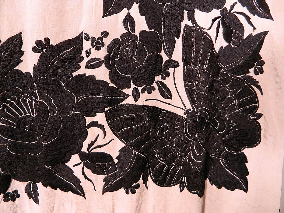 Antique Black & White Floral Butterfly Silk Embroidered Canton Piano Shawl. There is a fabulous floral rose, dragonfly embroidered border with a large beautiful butterfly embroidered in each corner. There is a hand knotted macramé black silk fringe which measures 24 inches long surrounding the entire shawl with rounded corners.