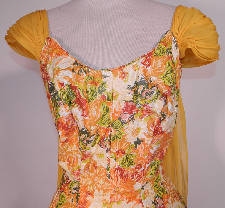 Vintage Edson's Hotel Syracuse Yellow Chiffon Scarf Floral Print Cotton Circle Skirt Dress. There is a golden yellow color silk chiffon pleated cap sleeve and long scarf drape down the back. This sensational summer dress has a low scoop neckline, short cap sleeves, fitted waist, full circle skirt and back zipper closure.