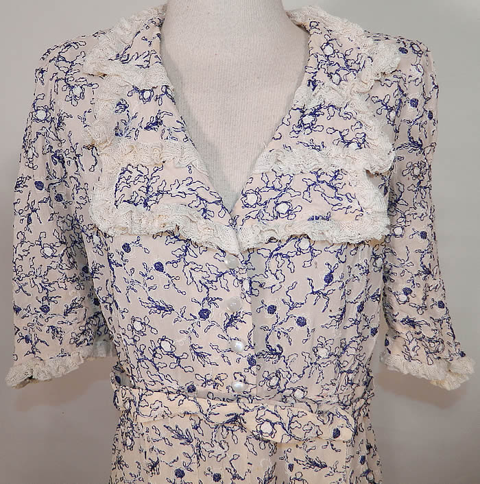 Vintage White Cotton Lace Blue Embroidered Stitching Belted Swing Day Dress. It is made of a white cotton fabric, with blue & white raised stitching soutache embroidery work done in a floral vine leaf design and white lace trim edging the collar and cuffs.