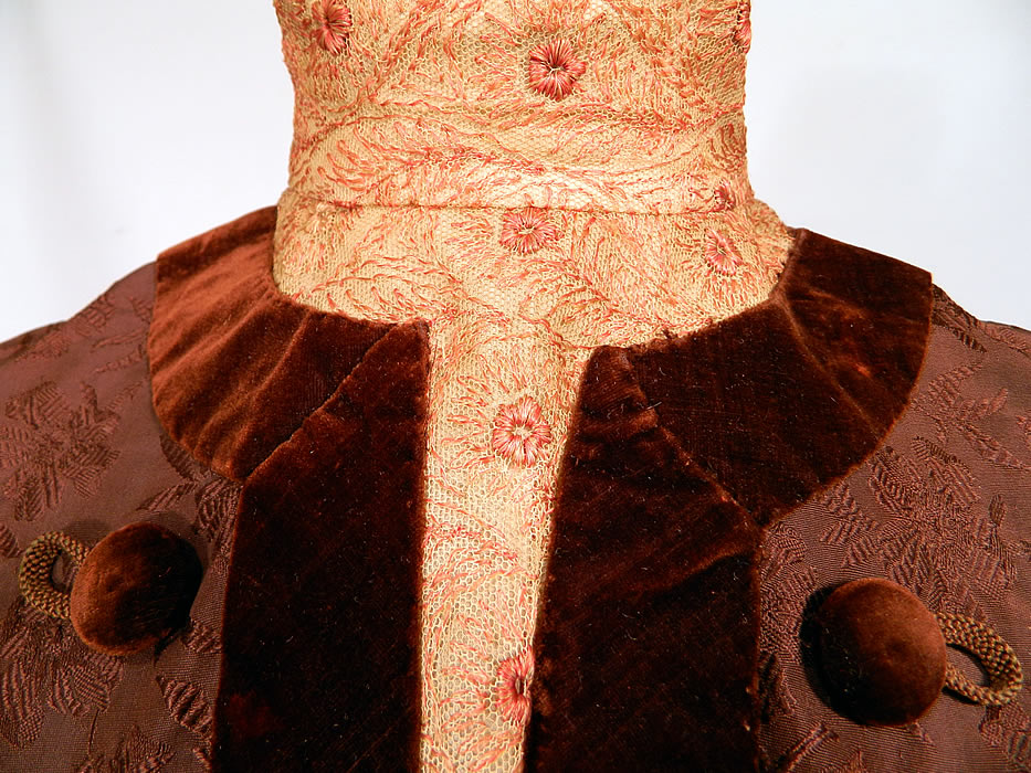 Edwardian Brown Silk Damask Floral Brocade Embroidered Lace High Collar Dress Gown. It is made of a dark chocolate brown color silk damask floral pattern brocade fabric, with brown velvet button trim edging and an off white cream color net lace pink embroidered yoke high neck collar insert and cuffs.