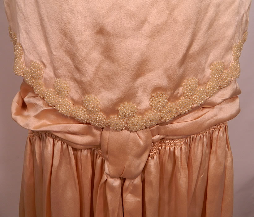 Vintage Cream Silk Pearl Beaded Handkerchief Scalloped Skirt Drop Waist Wedding Dress. This beautiful bridal wedding gown dress is loose fitting, has a drop waist, with attached sleeveless overblouse top, a belted sash waist with pleated gathering, an uneven handkerchief scalloped hem full skirt and lined top.