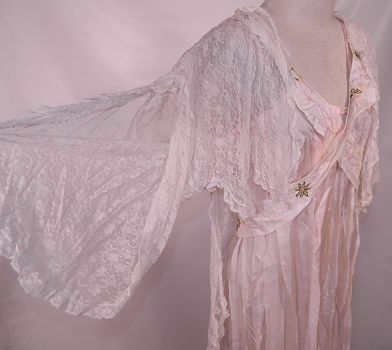 Edwardian Titanic Pink Silk Smocking White Lace Peignoir Negligee Nightgown Robe. This beautiful boudoir peignoir negligee nightgown style robe dressing gown is loose fitting, a long floor length with a scalloped hemline, crisscrossing silk straps on the top, a belted sash back, snap closures on the front, open bottom skirt and an attached sheer lace bed jacket blouse top with wide flared full sleeves, a longer back with scalloped bottom.