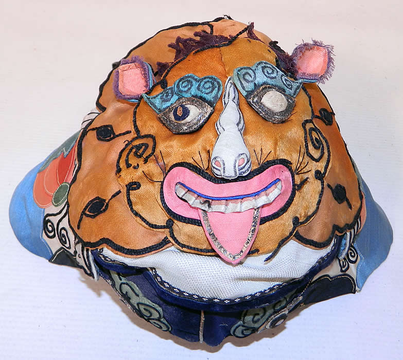 Antique Chinese Child Infant Silk Applique Tiger Wind Hat. The hat measures 18 inches long and 16 inches in circumference around the face. It is in good condition, with only minor wear to the silk fabric, some loose trim and is missing a pupil eye