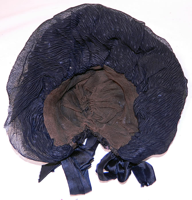 Victorian Black Silk Crepe Pink Flower Trim Mourning Bonnet Hat. This beautiful bonnet has black silk ribbon ties for securing under the chin. It is fully lined in a muslin fabric. The bonnet measures 25 inches in circumference. It is in good condition. This is truly a wonderful piece of wearable millinery art!