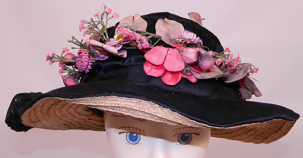 Edwardian Black Silk & Natural Straw Floral Garland Trim Wide Brim Hat. The hat is made of a black silk fabric, with a woven natural straw brim underneath. There is black silk soutache ribbon work trim along the back, side and a pink flower leaf garland wreath trim hatband.