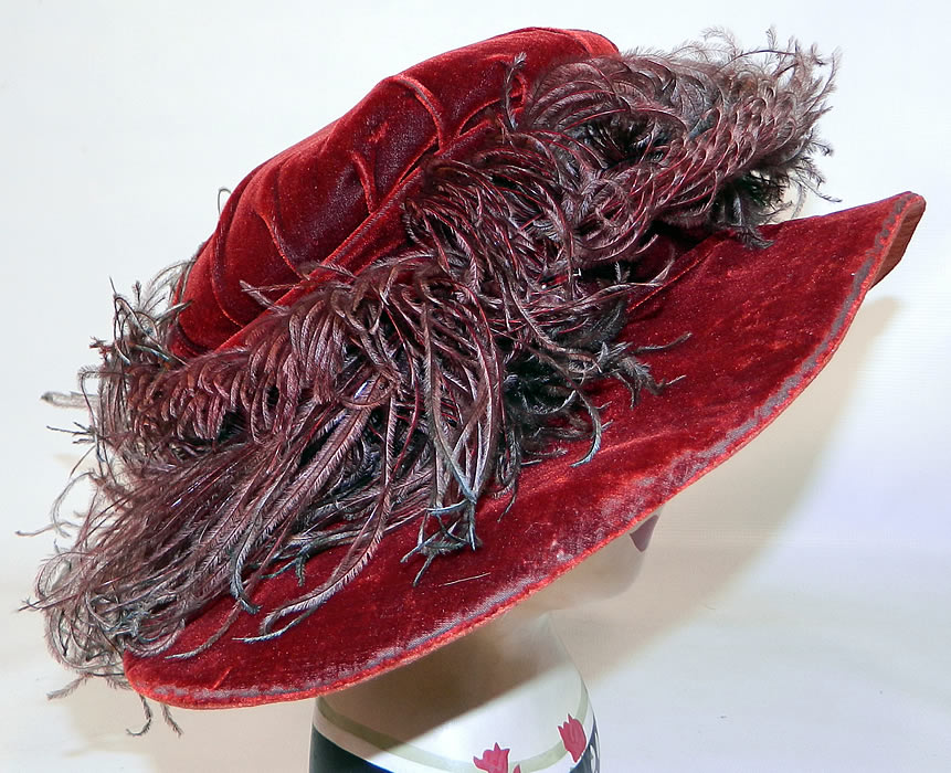 Vintage Fall Color Burgundy Red Velvet Feather Boa Trim Wide Brim Cloche Hat. The hat is made of a dark red burgundy wine color velvet fabric, with ombre color brown to green ostrich feather boa trim surrounding the crown.