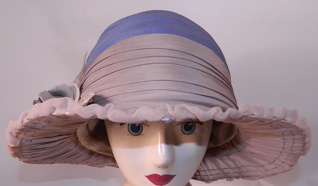 Vintage Maurice Importer Gray & Blue Silk Rose Flower Wide Brim Cloche Hat. It is made of a gray and blue silk fabric, with a blue velvet rose flower trim on the side.