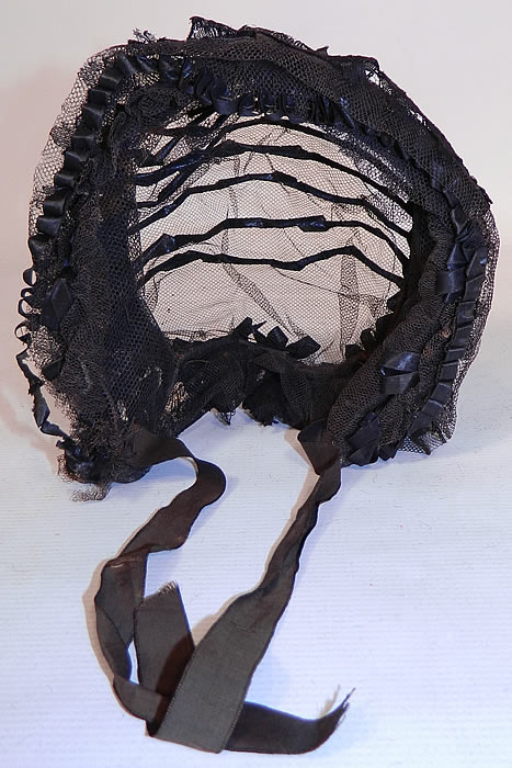Victorian Civil War Era Black Net Ribbon Trim Mourning Bonnet Snood Headdress. The bonnet measures 17 inches around the front face and is 12 inches deep from front to back. It is in good condition, with only some slight fraying of the silk ties at the chin. This is truly a wonderful rare piece of antique mourning millinery art!