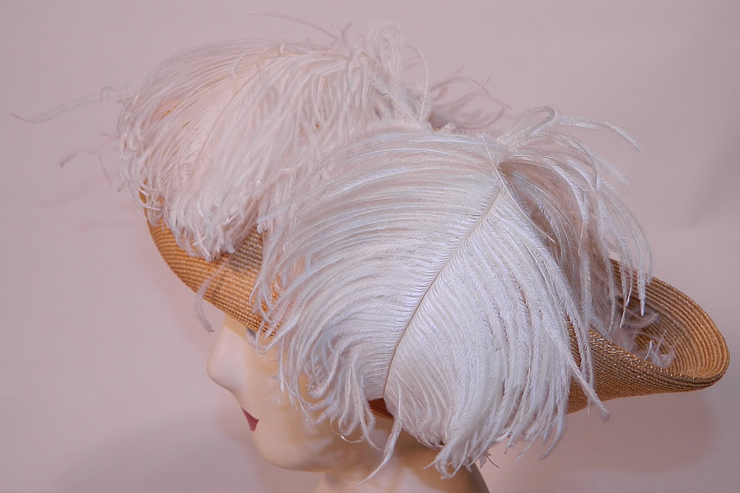 Edwardian Titanic Natural Straw Upturned Wide Brim White  Ostrich Feather Hat. It is made of a tightly woven natural straw basket weave, with white fluffy ostrich feather plume trim around the crown.