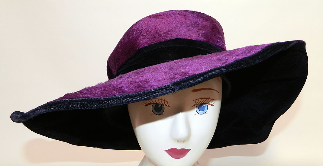 Edwardian Vintage Wolf Millinery Purple Velvet Flower Trim Wide Brim Hat. It is made of a dark purple plum plush silk velvet fabric, with a black velvet ribbon hatband, purple and orange wired pipe cleaner chenille flower trim decorating the sides.