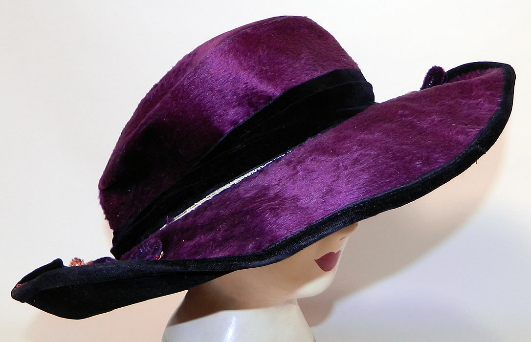 "Edwardian Vintage Wolf Millinery Purple Velvet Flower Trim Wide Brim Hat. This pretty purple  plum hat has  an uneven asymmetrical oval shaped wired wide brim, which is wider along the sides and front, narrow in the back, with a black velvet backing underneath and a black silk lining inside the crown, with a ""Wolf Millinery 216 N. Duke St. Lancaster, PA"" label."