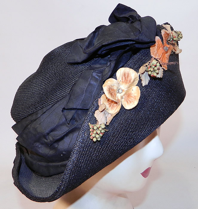Edwardian Black Straw Orange Silk Velvet Floral Trim Upturned Wide Brim Hat. The hat is made of a black tightly woven straw, with orange silk velvet flower, leaf and berry garland trim on the front brim and a black silk ribbon hatband with bow trim front.