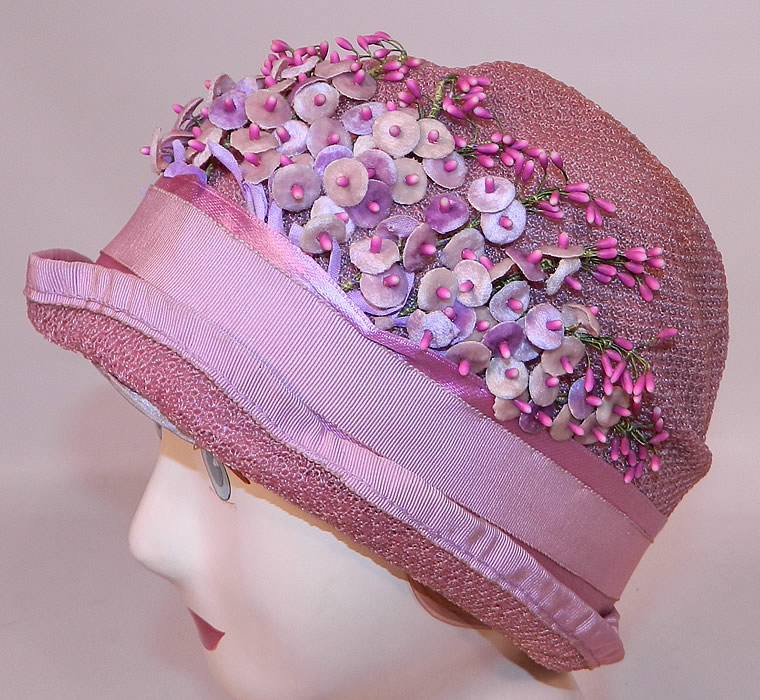Vintage Tenne Hats Purple Lilac Woven Straw Lavender Flower Flapper Cloche. It is made of a pale purple lilac color woven straw fabric, with pink grosgrain silk ribbon trim edging around the brim, hatband and tiny velvet lavender flowers, blossoms trimming the front.