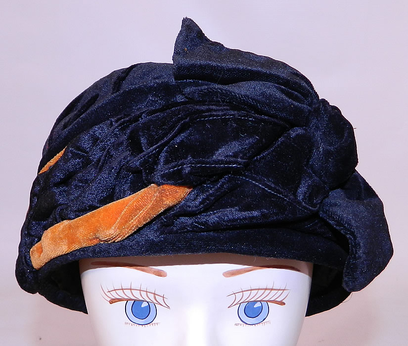 Vintage Art Deco Black & Orange Velvet Knotted Bow Trim Flapper Cloche Hat. The hat is made of black and orange silk velvet fabric, with a draped, wrapped design around the outside and a knotted bow trim on the front.