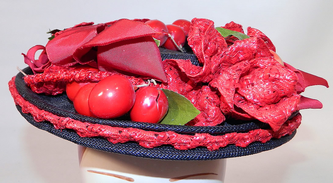 Vintage Red Straw Roses Cherries Small Skimmer Boater Tilt Hat Fascinator. It is made of a navy blue tight weave straw base, with red woven straw rose flowers, red plastic cherry fruit and a red silk grosgrain ribbon hatband bow trim.