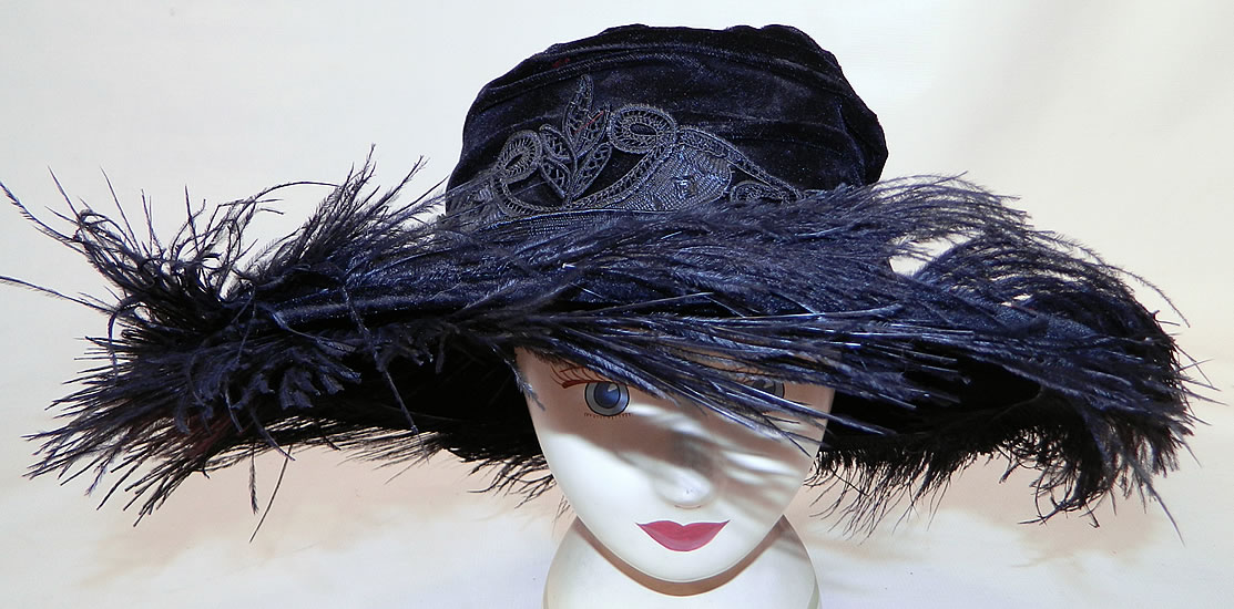 Edwardian Vintage Madame Gatecliff Modiste Black Velvet Lace Feather Trim Wide Brim Hat. It is made of a black velvet fabric, with black silk battenburg tape lace applique trim sewn around the crown and black ostrich feather plumes sewn around the brim.
