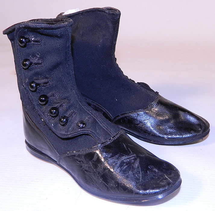 Victorian Black Wool Leather High Button Button Baby Boots Childs Shoes. They are made of a two tone black wool fabric top and black patent leather bottom shoe, with 7 black buttons down the side for closure.