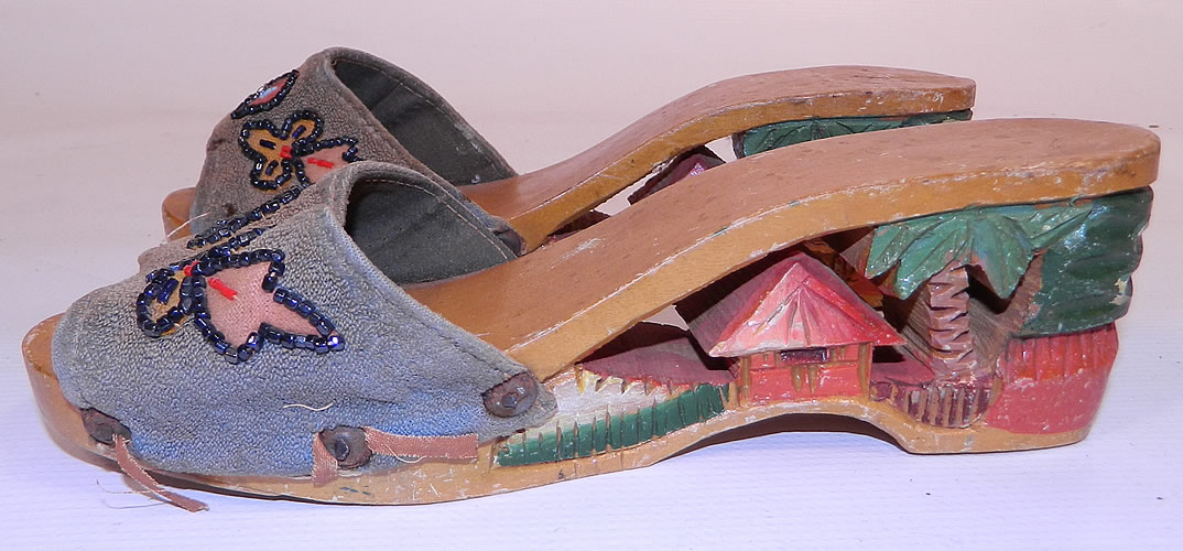 Vintage Philippines Hand Painted Carved Wooden Wedge Mules Sandal Shoes. This pair of vintage Philippines hand painted carved wooden wedge mules sandal shoes date from the 1940s. They are made of a hand painted carved wood, with a cut out tropical hut, palm tree heel and hand beaded blue fabric across the instep front vamp.