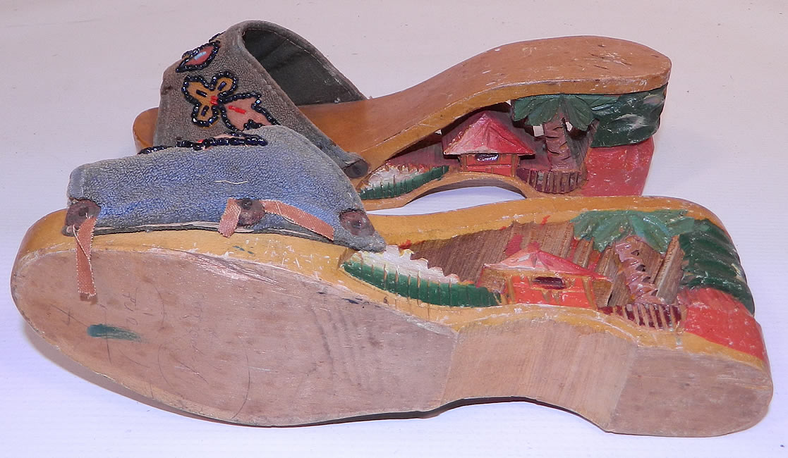 Vintage Philippines Hand Painted Carved Wooden Wedge Mules Sandal Shoes. They are in good condition, with some wear, dings and nicks on the wood and the trim edging along the fabric vamp sides is frayed and loose. These would make a great display piece and are truly a wonderful piece of hand crafted wearable retro shoe art!