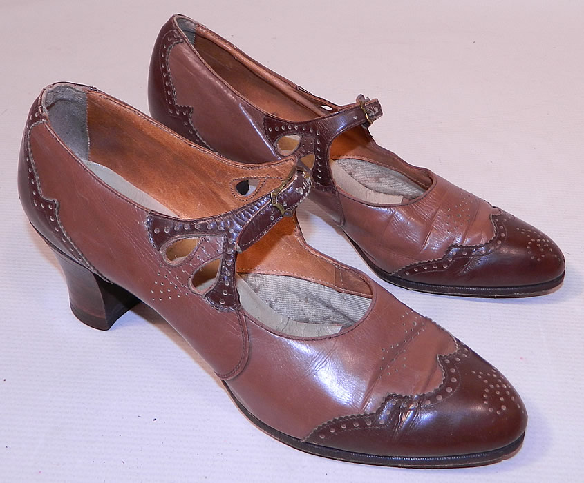 Vintage Two Tone Punchwork Brown Leather Buckle Strap Mary Jane Shoes. This pair of vintage two tone punchwork brown leather buckle strap Mary Jane shoes date from the 1920s. They are made of two tone brown color leather with decorative punchwork, scalloped trim edging details.