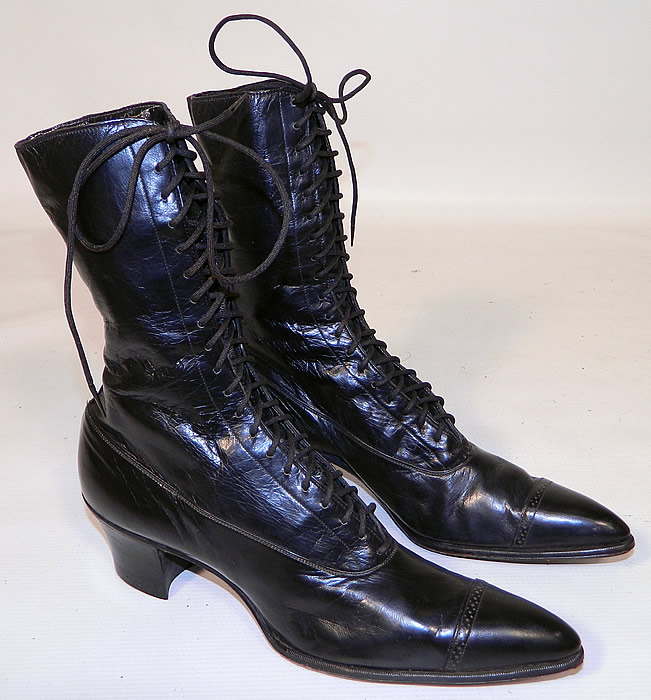 Vintage Poehlman Shoe Co Unworn Victorian Black Leather High Top Lace-up Boots. The boots have pointed toes, the original black shoe string laces for closure and black stacked wooden cube heels.