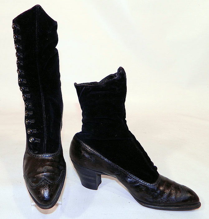 Victorian Black Velvet & Leather High Top Button Boots WH Tuttle Co Boston. The boots have pointed toes with decorative punch work designs on the front toes, 14 black shoe buttons along the side for closure and stacked black wooden cube heels.