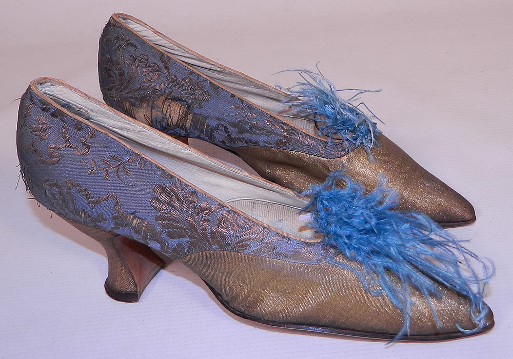 Edwardian Titanic Blue Silk Gold Lamé Damask Brocade Feather Trim Shoes. They are made of a blue silk damask, floral leaf brocade patterned gold metallic lamé fabric. These beautiful brocade fancy evening shoes have blue ostrich feather trim pompoms on the front instep vamps, a slip on style, with pointed toes and gold lamé covered French Louis XV spool heels.