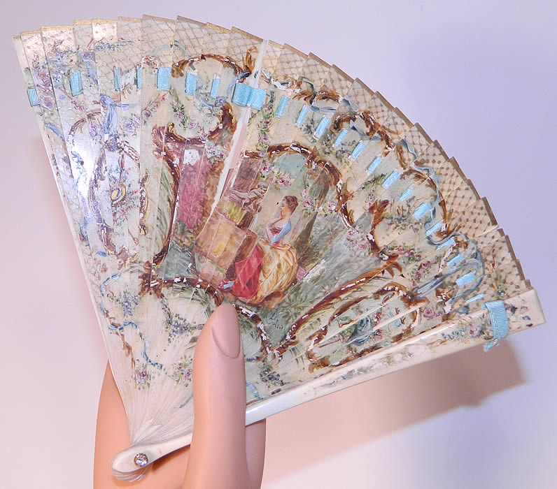 Victorian Antique Hand Painted Figural Bone Small Brise Dance Fan. It is made entirely of a carved bone sticks, with a hand painted 18th century figural floral design on the front, a blue ribbon bow floral garland design on the back and gold gilt accents.