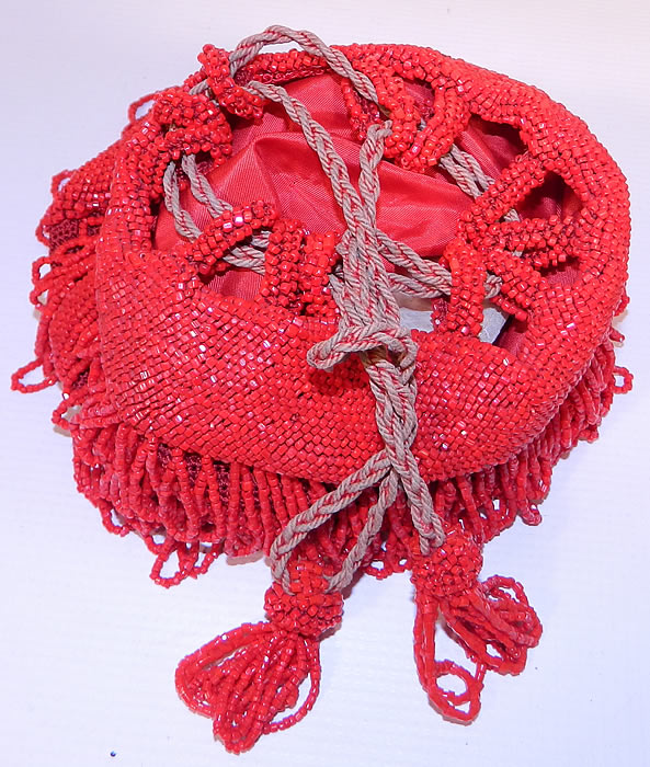 Antique Art Deco Red Beaded Loop Fringe Tassel Drawstring Flapper Purse.This fabulous flapper handbag purse has a drawstring closure on top with silk rope straps. It is fully lined in a red silk fabric inside. The purse measures 9 inches long and and 7 inches wide. It is in excellent condition.