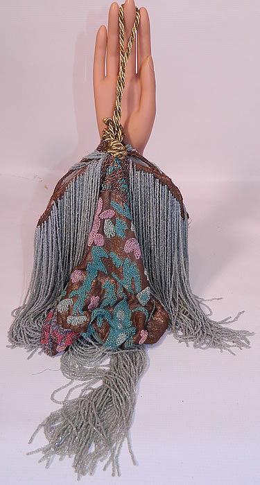 Antique Art Deco Gold Lamé Pastel Beaded Flapper Dress Fabric Fringed Purse. This antique Art Deco gold lamé pastel beaded flapper dress fabric fringed purse dates from the roaring 1920s. It is made of a gold metallic lamé fabric, with colorful pastel hand bead work done in an abstract Art Deco design floral pattern and baby blue color long heavy beaded fringe trim.