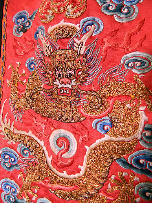 "Antique Chinese Chaoqun Court Apron Skirt Panel Embroidered Gold Dragon. There is a front facing gold ""Long"" five clawed dragon, with smoke clouds, flames, pearl, bat and waves of water along the bottom. The dragon symbolizes the emperor, who was regarded as the Son of Heaven. There is a black silk trim border edging with blue and white embroidered flowers, butterflies and a knotted fringe tassel trim hanging down from the bottom."