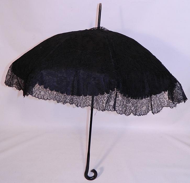 Edwardian Black Chantilly Lace Carved Ebony Handle  Parasol. There is a carved black ebony wood curled handle and metal capped tip finial top. This pretty parasol umbrella is lined in black silk, with a black metal frame inside.
