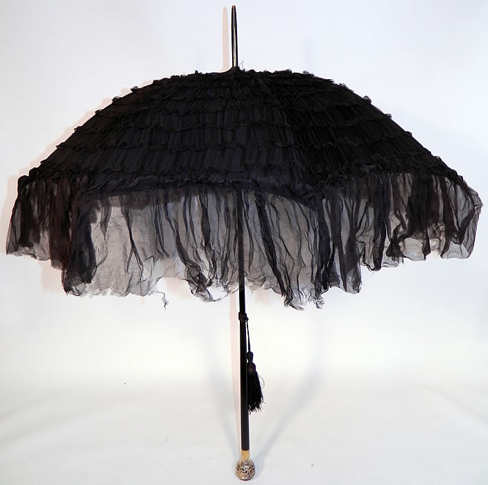 Edwardian Black Silk Ruched Ebony Amethyst Jeweled Handle Parasol. This Edwardian era antique black silk ruched ebony amethyst jeweled handle parasol dates from 1910. It is made of black silk chiffon fabric with decorative ruched tucks, gathers, pleating and a sheer ruffle trim edging.