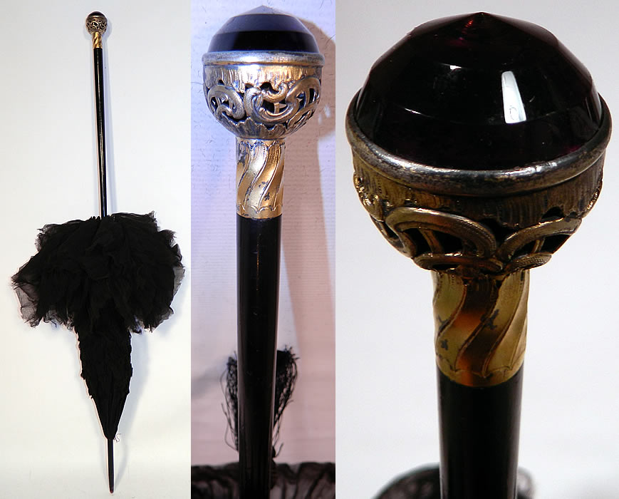 Edwardian Black Silk Ruched Ebony Amethyst Jeweled Handle Parasol. There is a black ebony wood stick handle and finial top, with a jeweled amethyst gold tone metal filigree round ball base handle and black silk tassel trim.
