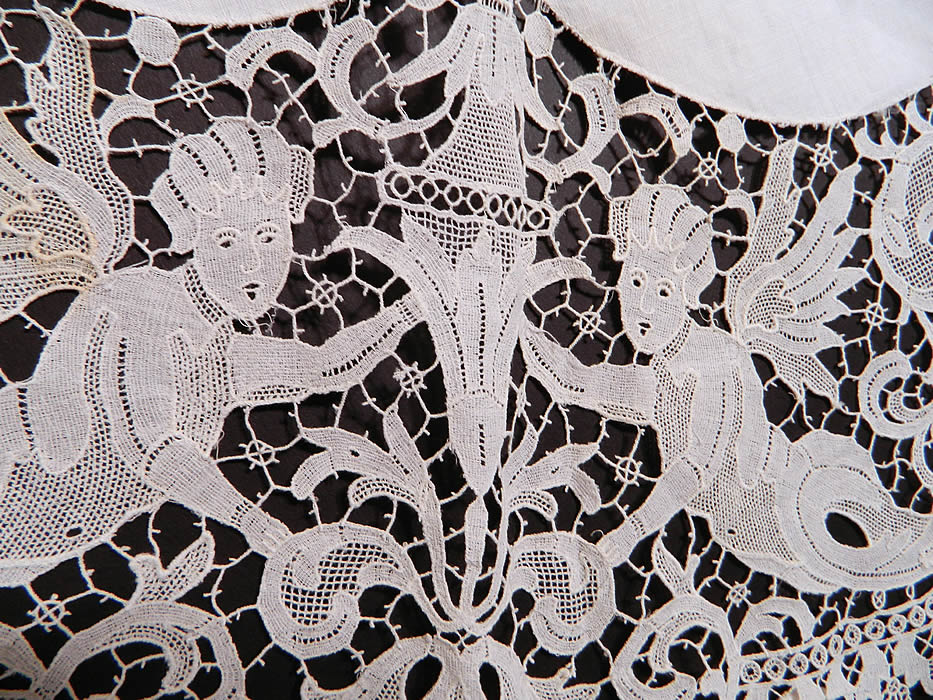 Victorian Antique Point de Venise Lace Renaissance Cupid Linen Round Tablecloth.  It is in good condition, but has not been cleaned, with only a few tiny faint age spot stains. This is truly a wonderful piece of antique lace textile art!
