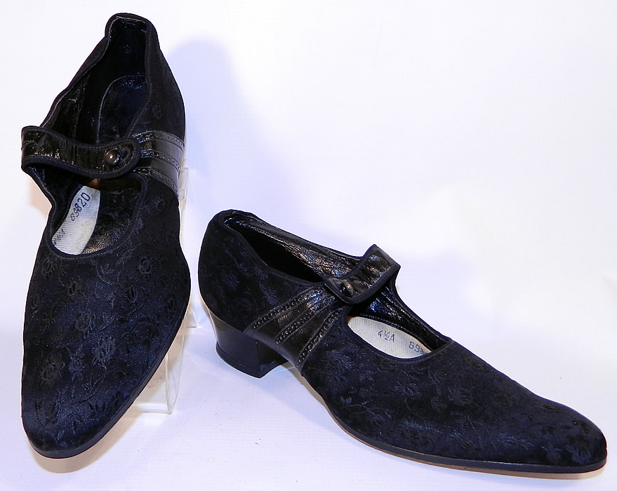 Unworn Vintage Black Silk Brocade Patent Leather Mary Jane Button Strap Shoes. They are made of black silk damask floral brocade fabric, with black patent leather trim across the instep.